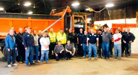 Public Services staff standing in front of a dump truck